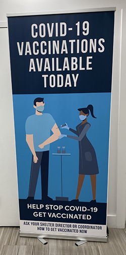 Picture of a blue pop-up sign located in a HELP USA shelter advertising that COVID-19 Vaccinations are available to residents and staff. The sign features an illustration of a nurse administering a shot in the arm of a man.