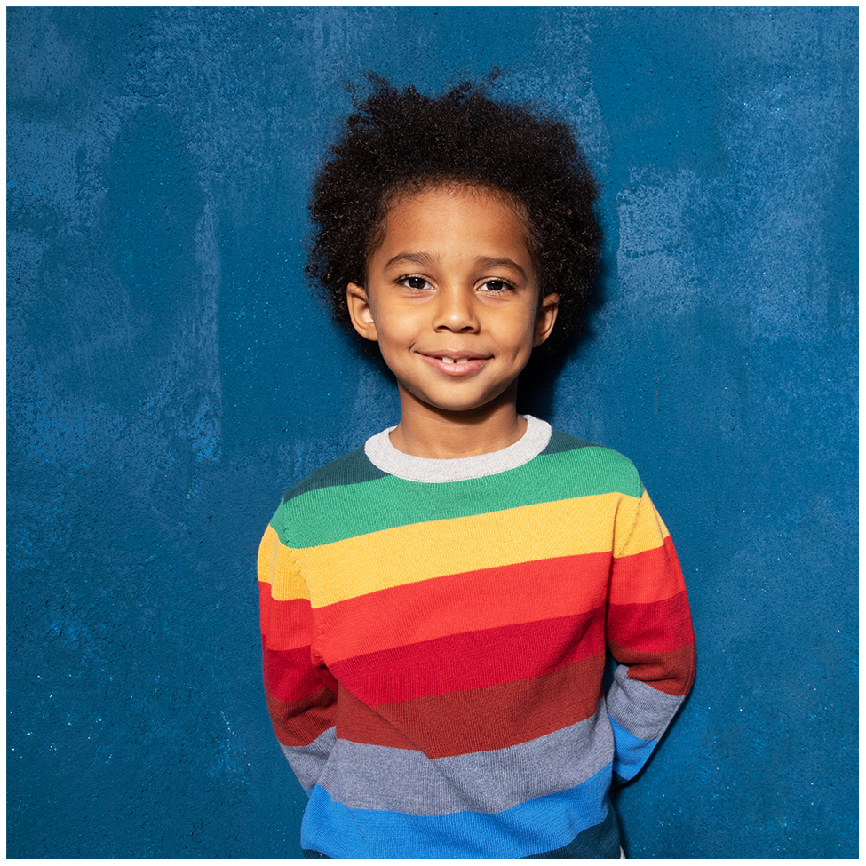 A boy in a multi-colored striped sweater standing against a blue wall.